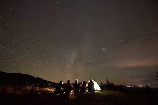 Вид сзади пяти человек, сидящих в туристической палатке на копии пространства темного звездного неба.
