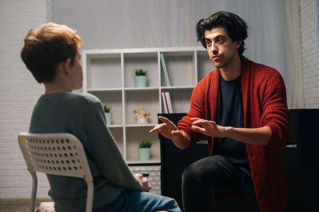 Вид сзади сосредоточенного школьника, сидящего на стуле, слушающего молодого учителя музыки, говорящего и жестикулирующего