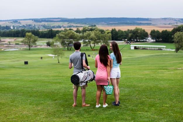 Вид сзади друзей на поле для гольфа