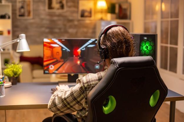 늦은 밤 거실에서 강력한 pc 컴퓨터로 슈팅 게임을 하는 남성 게이머의 뒷모습.