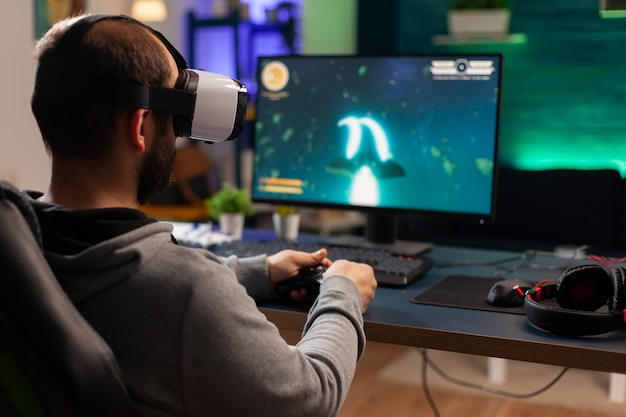 Вид сзади игрока, играющего в космический шутер с очками виртуальной реальности. соревновательный игрок, использующий джойстик для онлайн-чемпионата, сидит на игровом стуле поздно ночью в гостиной