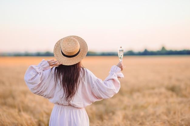 麦畑の女の子の背面図。手で熟した小麦と麦わら帽子のドレスを着た美しい女性