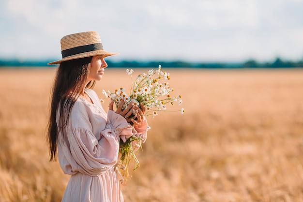 麦畑の女の子の背面図。麦わら帽子のドレスを着た美しい女性