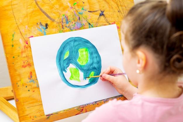 소녀의 뒷모습은 이젤에 종이에 붓으로 지구를 그리고 있습니다. 지구의 날의 개념입니다.