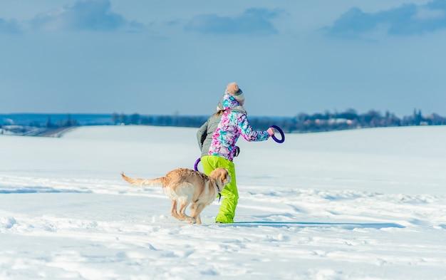 犬と一緒に雪の中を走っている少女の背面図