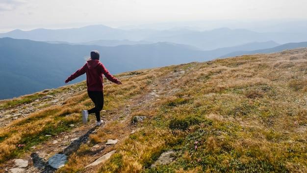 Вид сзади девушки, бегущей по горной долине