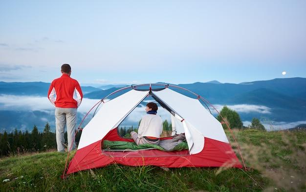 Вид сзади девушка сидит в палатке, а парень стоит рядом с красивым пейзажем