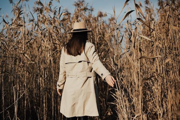 背景に青い空と乾燥した葦の茂みにベージュのトレンチコートと帽子を持つ少女の背面図。