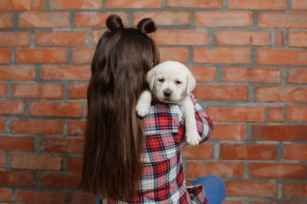 かわいい1ヶ月のゴールデンレトリバーの子犬の犬を保持している長い髪の少女の背面図