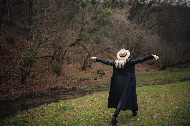 静かに川の岸を歩いている腕を上げた少女の背面図。