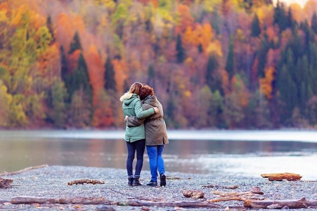 가을 산과 아름다운 일몰을 감상하는 호수를 바라 보는 소녀의 뒷모습