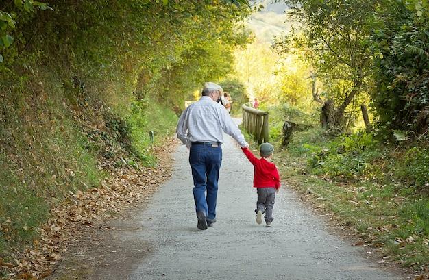 자연 경로를 걷고 할아버지와 손자의 뒷면