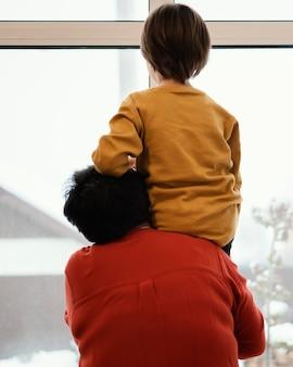 窓越しに見ている祖母と孫の背面図