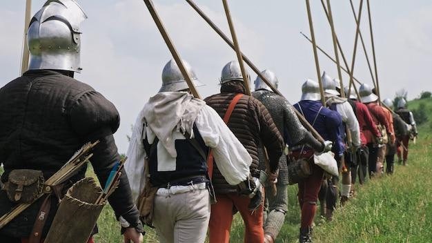 Вид сзади группы средневековых рыцарей, идущих на бой. воины идут с копьями, мечами, луками и шлемами на головах. историческая реконструкция xiv-xv веков, фландрия.