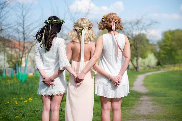 Вид сзади группы подружек невесты с будущей невестой в красивых