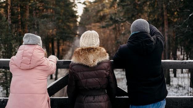 冬の屋外の友人のグループの背面図