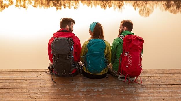 カラフルな暖かい服を着て、湖の近くの木製の桟橋に座って、秋の自然の中で一緒にトレッキングした後に休んでいるバックパックを持った若いハイカーのグループの背面図