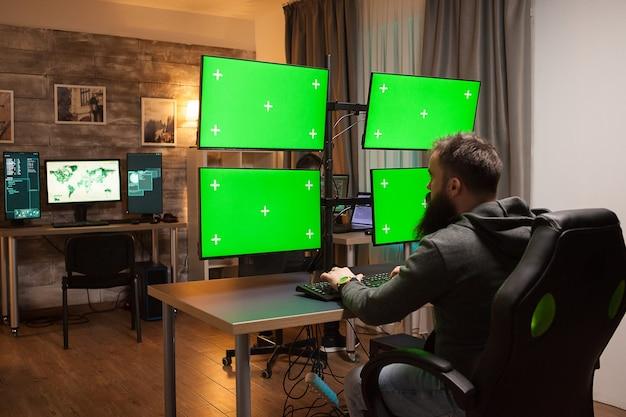 緑のモックアップで複数の画面を持つコンピュータの前にハッカーの背面図。