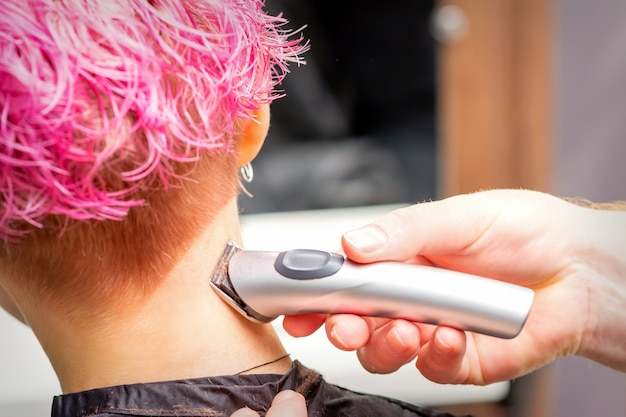Вид сзади руки парикмахера, бреющей затылок и шею электрическим триммером молодой кавказской женщины с короткими розовыми волосами в салоне красоты.