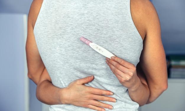 女性の手が妊娠検査陽性