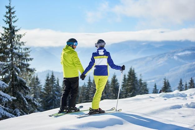 山の端に立って、手をつないで、冬の山のパノラマ風景を楽しむ幸せなカップルのスキーヤーの背面図