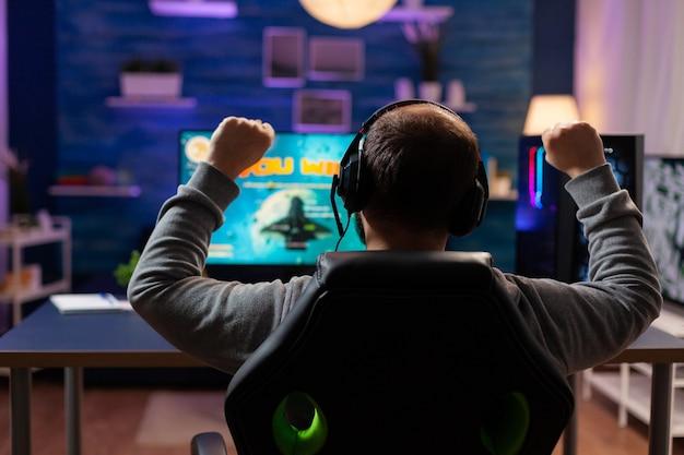 ゲームのホームルームでスペースシューターゲームをプレイして勝利した幸せなゲーマーの背面図。オンラインチャンピオンシップのためにプロのヘッドフォンを使用して、強力なコンピューターストリーミングビデオゲームでサイバーパフォーマンスを行う