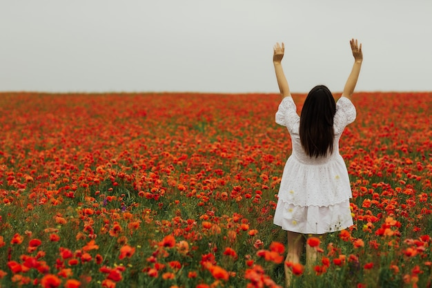 夏の日の赤いポピーの花で幸せな女の子の背面図