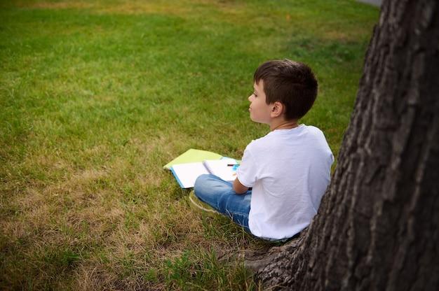 放課後、都市公園の緑の芝生に座って、木にもたれて、宿題をして、彼の環境に気を取られて休んでいる幸せな男子生徒の背面図。学校に戻る