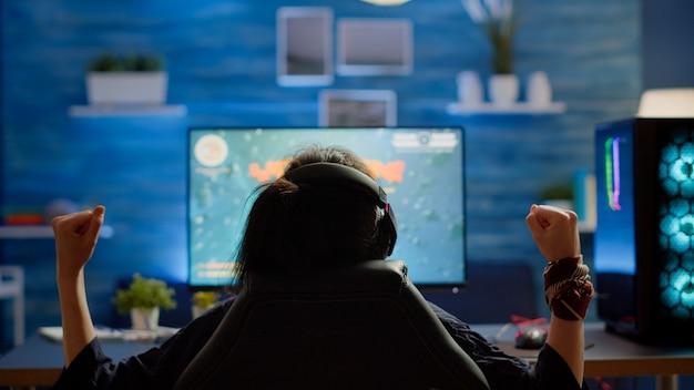 ゲームのホームルームでスペースシューターゲームに勝つ幸せな女性ゲーマーの背面図。オンラインチャンピオンシップにプロのヘッドフォンを使用したrgbパワフルなコンピューターストリーミングビデオゲームでのサイバーパフォーマンス
