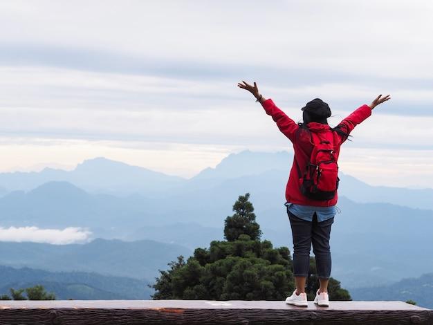Вид сзади счастливой женщины-туриста, поднимающей руки над видом на горы и голубое небо с туманом