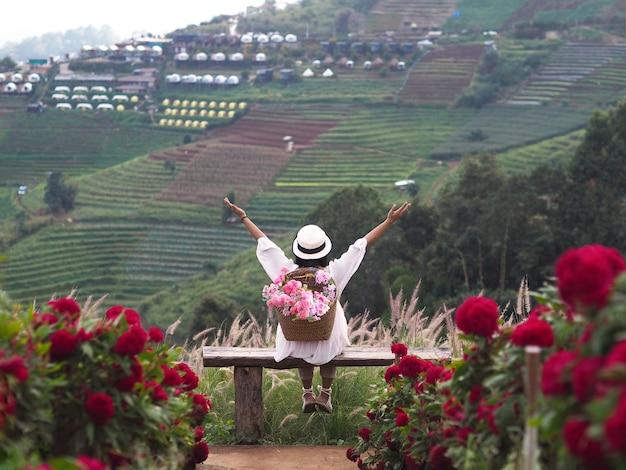 Вид сзади счастливой женщины-туриста сидит на скамейке и поднимает руки в поле цветов в королевском проекте мон чам и нонг хой, чиангмай, таиланд.
