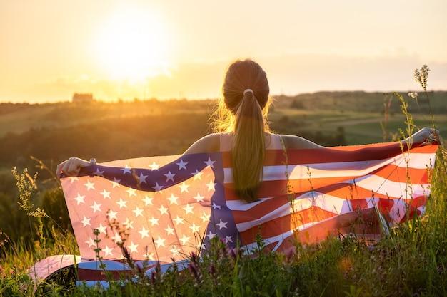 미국 국기가 일몰에 야외에 앉아 있는 행복한 여성의 뒷모습. 미국 독립 기념일을 축하하는 긍정적인 소녀. 국제 민주주의의 날 개념.