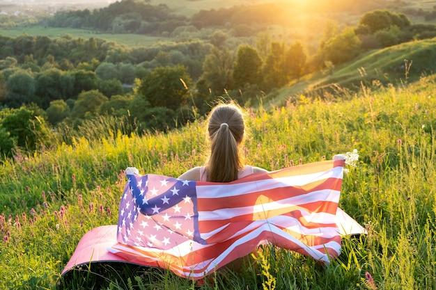Вид сзади счастливая женщина с национальным флагом сша, сидя на открытом воздухе на закате.