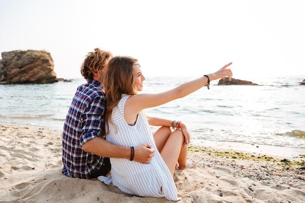 Вид сзади счастливой молодой пары, сидящей и указывающей в сторону на пляже