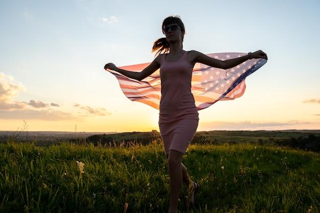 Вид сзади счастливой молодой женщины, позирующей с национальным флагом сша на открытом воздухе на закате. положительная женщина празднует день независимости соединенных штатов. международный день демократии концепции.