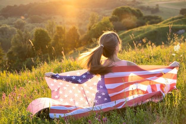 Вид сзади счастливой молодой женщины, позирующей с национальным флагом сша на открытом воздухе на закате.