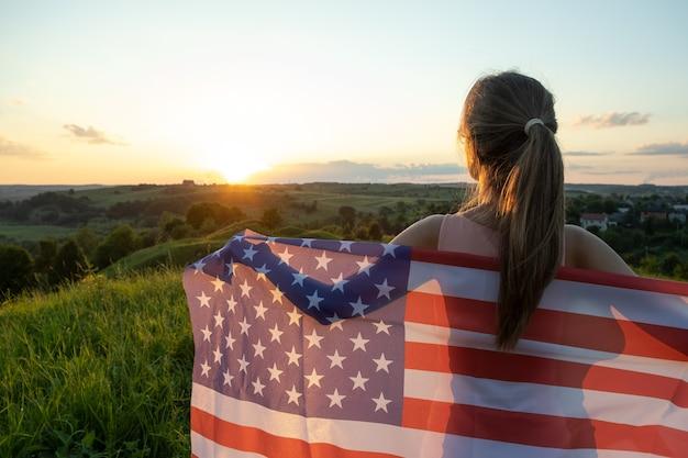 Вид сзади счастливой молодой женщины, позирующей с национальным флагом сша, стоящим на открытом воздухе на закате. позитивная девушка празднует день независимости соединенных штатов. международный день демократии концепции.