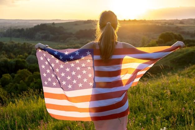 일몰에 야외 서 미국 국기와 함께 포즈를 취하는 행복 한 젊은 여자의 뒷면