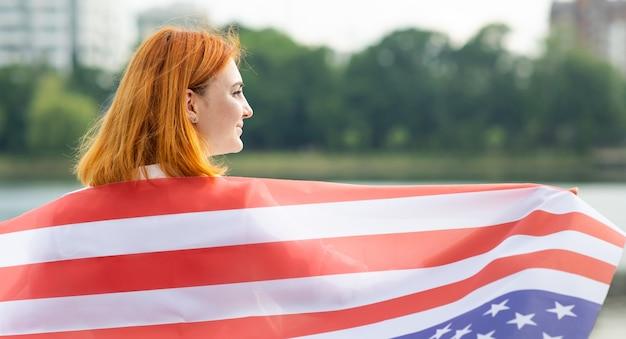 彼女の肩に米国国旗を持つ幸せな若い女性の背面図。アメリカ合衆国の独立記念日を祝うポジティブな女の子。
