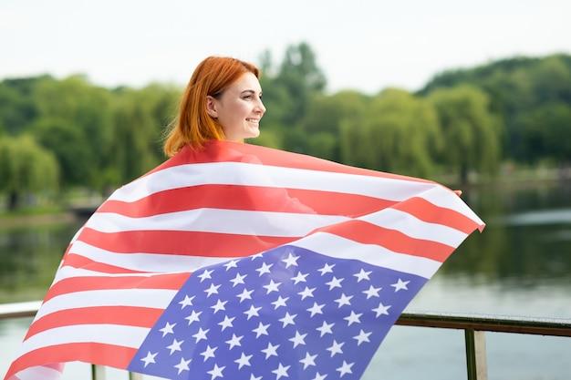 Вид сзади счастливой молодой женщины с национальным флагом сша на ее плечах.