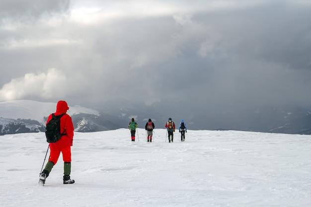 겨울 산에서 눈 덮힌 언덕에 걷는 등산객의 뒷면.
