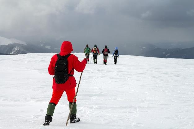 겨울 산에서 눈 덮힌 언덕을 걷는 등산객의 뒷면