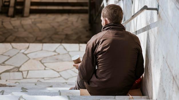Вид сзади бездомного с чашкой на лестнице
