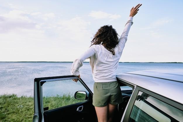 Вид сзади радостной молодой женщины в повседневной одежде, выходящей из машины и поднимающей руку, стоя перед озером или рекой