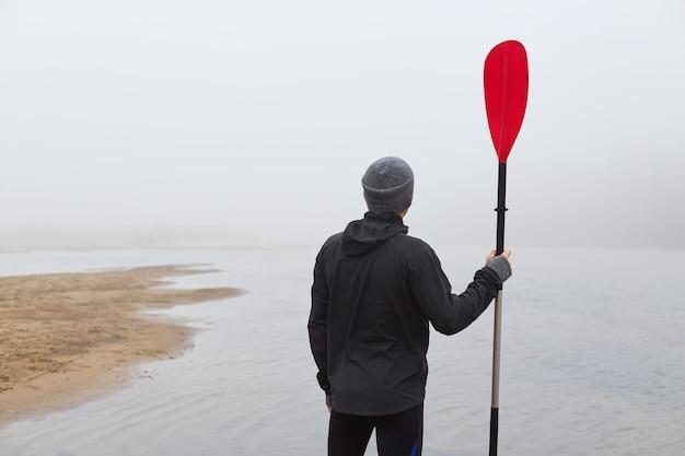 Вид сзади на каякинг на берегу реки с веслом в руках, глядя вдаль, наслаждаясь красивым туманным утром