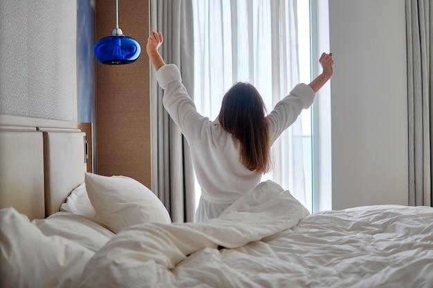 목욕 가운을 입은 게으른 여자의 뒷모습은 호텔 방에서 아늑한 편안한 침실에서 휴식을 취하는 동안 이른 아침에 좋은 잠에서 깨어납니다.