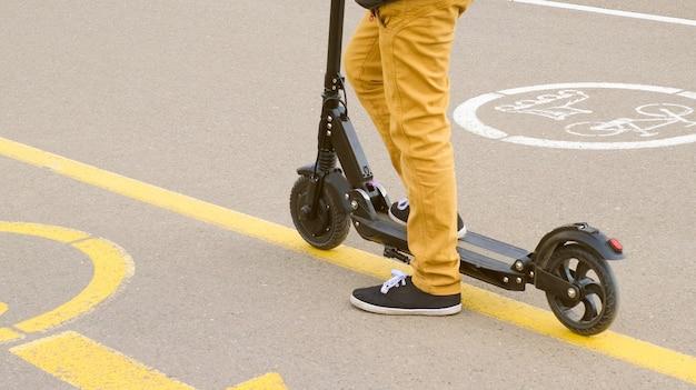 스쿠터에 노란색 바지와 검은 덧신에 소년의 다리의 후면보기를 닫습니다