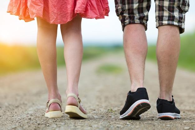 Вид сзади ног молодой стройной женщины в красном платье и мужчины в шортах, идущих вместе по грунтовой дороге в солнечный летний день на размытом фоне.