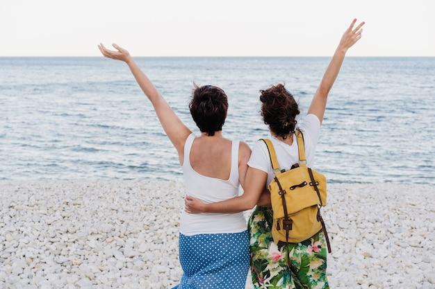 日没時にビーチで抱き締めるレズビアンカップルの背面図。腕を上げて幸せ。愛は愛であり、lgtbiの概念