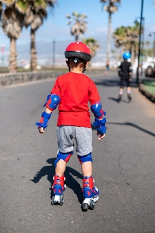 롤러 스케이트로 연습하는 어린 소년의 뒷면